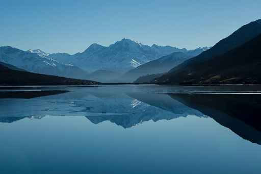 Photo of snowy mountain reflected on the still surface of a lake.