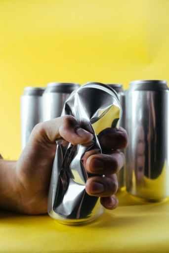 Hand crushing an aluminum can.