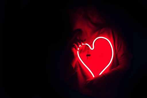 Red, heart-shaped neon sign in front of model's chest.