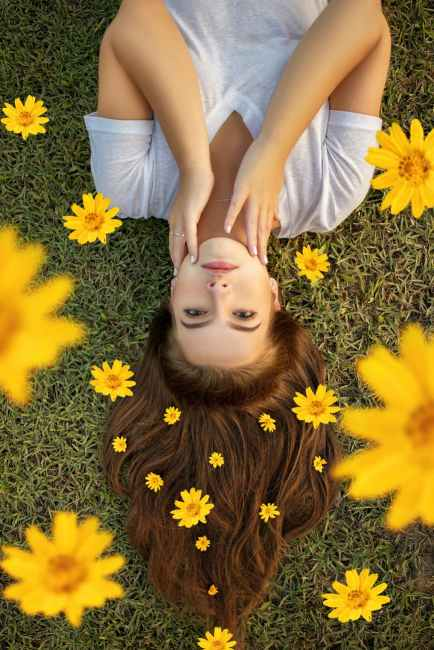 Inverted photo of a woman surrounded by daisies.