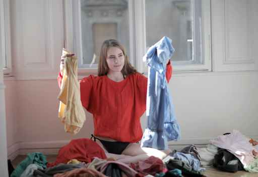 woman in red long sleeve shirt holding up clothes, using the power of choice to decide what to wear