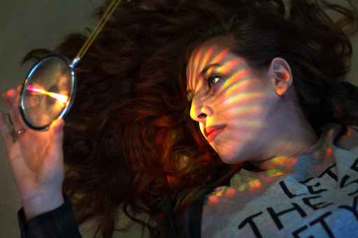 dreamy woman with magnifier and multicolored stripes on face focusing on why bad things happen to me