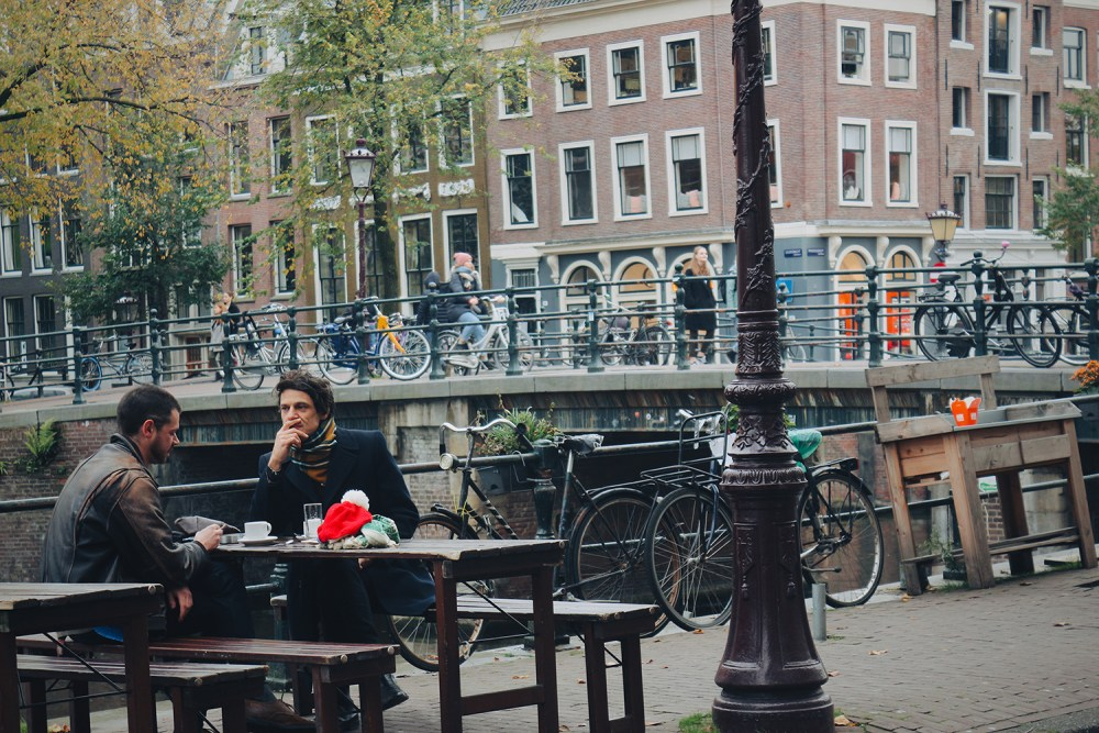 2 men sitting by the canal of Amsterdam