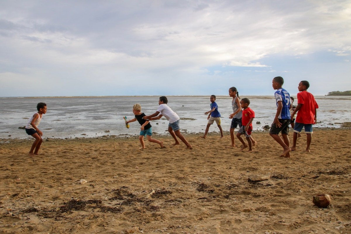 Playing rugby on the beach in Fiji with kids.
