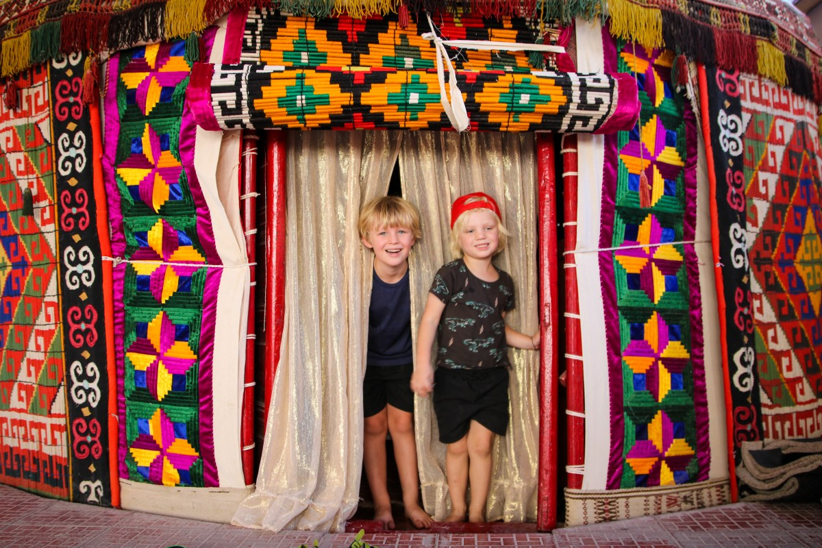 Inside a brightly coloured yurt in Uzbekistan with the kids.