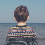 Boy looking at the sea in retro jumper