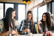 Young beautiful friends meet at the cafe