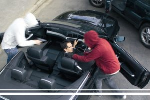 Two hooded people pull man in suit out of car
