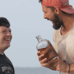 tyler and zack share whiskey on the beach in the peanut butter falcon movie