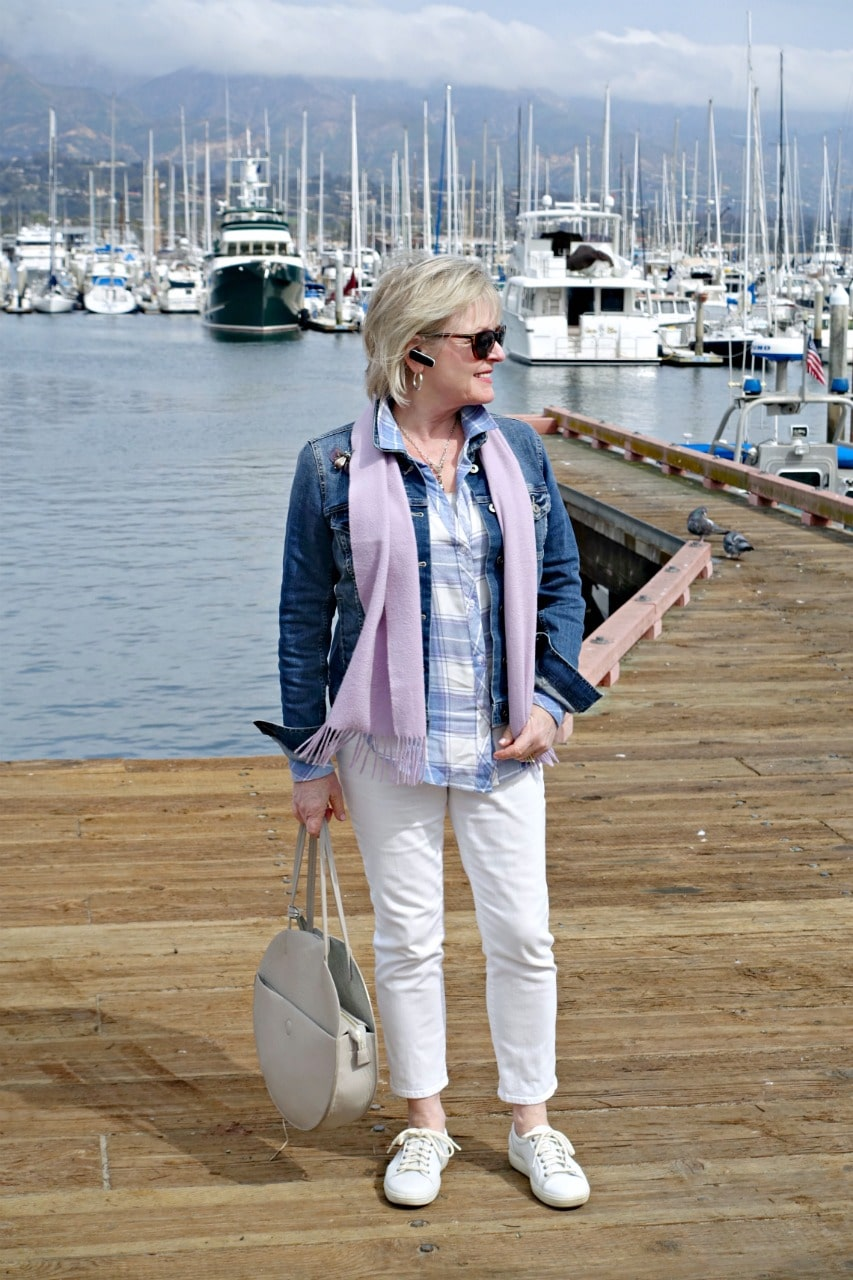 Jennifer of A Well Styled Life wearing white jeans, flannel shirt and denim jacket on pier in Santa Barbara
