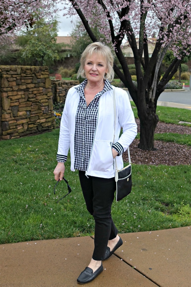 Jennifer Connolly of A Well Styled Life wearing black and white gingham shirt, black never fade jeans, black driving moccasins and white T Talbots yoga jacket from Talbots