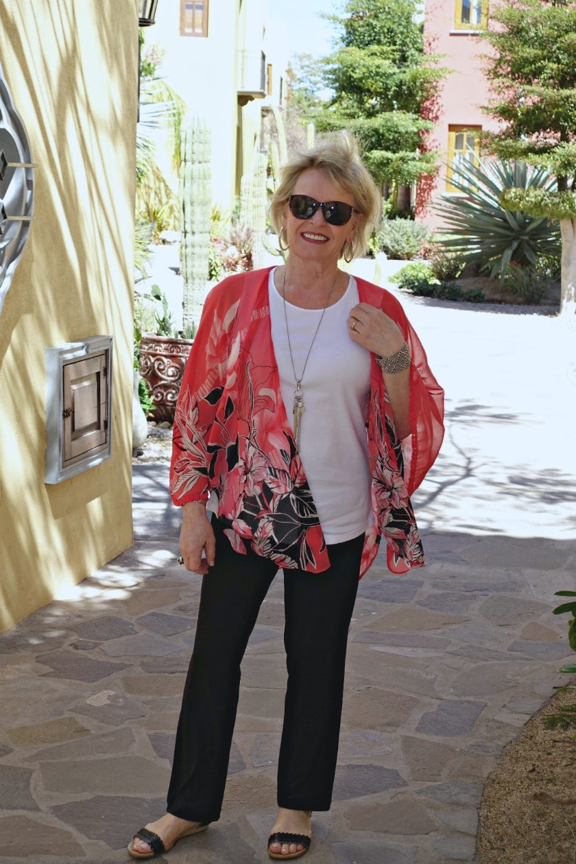 Jennifer of A Well Styled Life wearing floral ruana over white tank and black pants