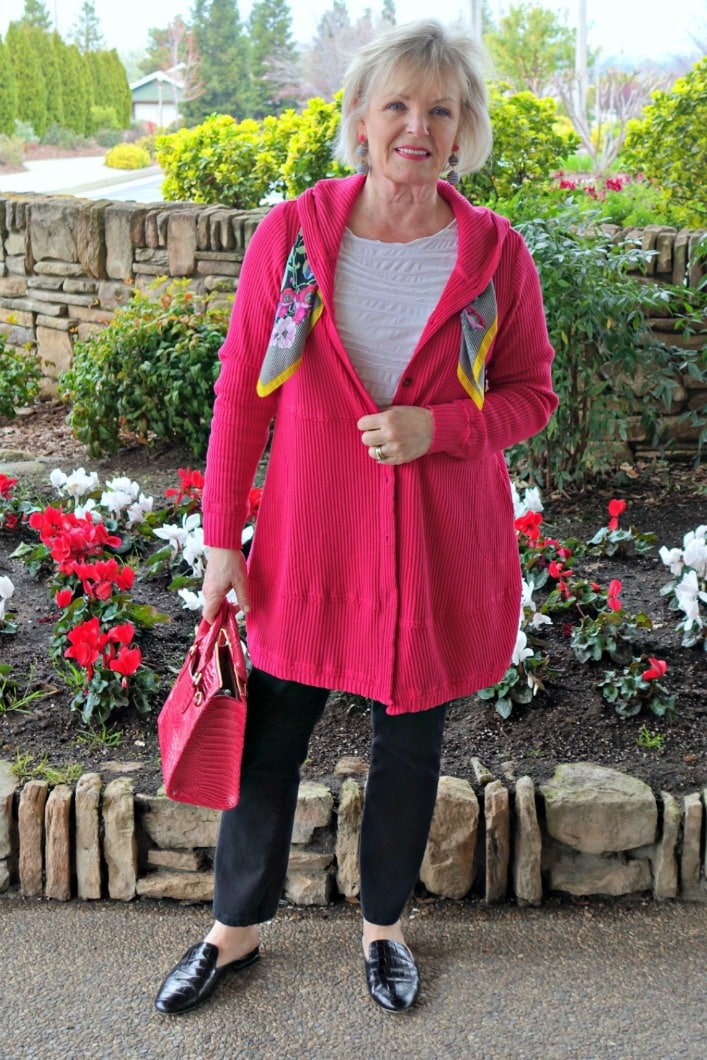 Jennifer Connolly from A Well Styled Life wearing a pomegranate colored hoodie, black jeans, black mules, white tunic and pink handbag