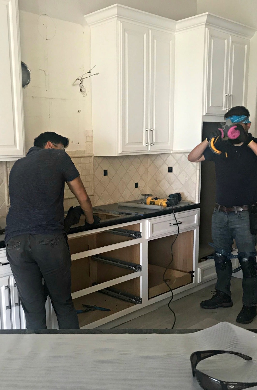 three men sawing existing granite counter to fit new stove on A Well Styled Life