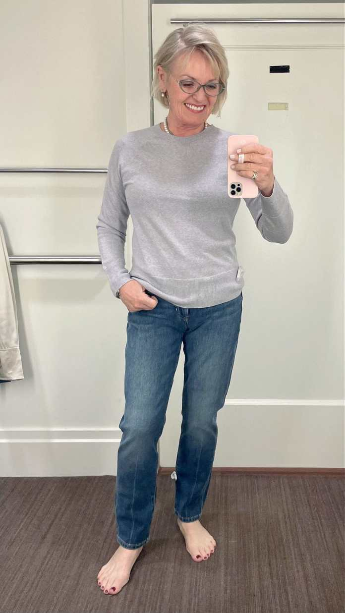 woman taking selfie wearing gray sweater and jeans