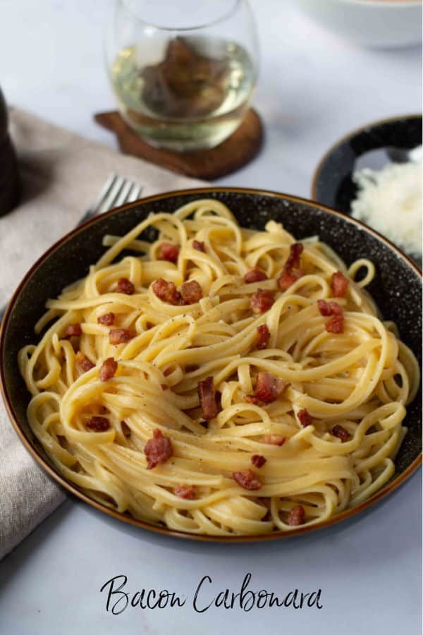 Bowl of Bacon Carbonara with wine