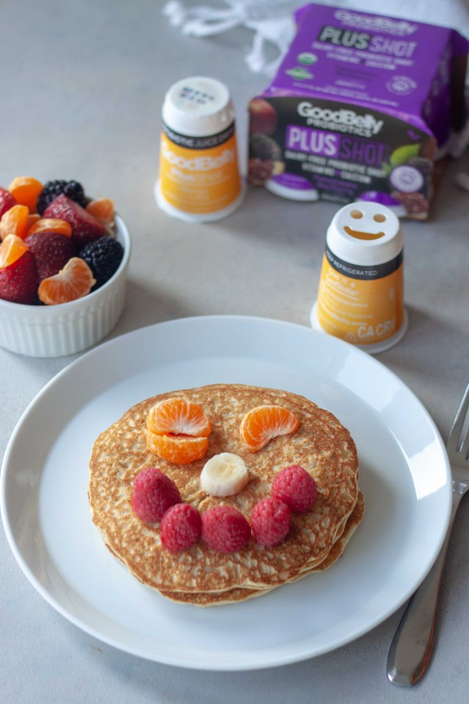 Oatmeal Pancakes topped with a smiley face made of fruit, served with GoodBelly Probiotics.