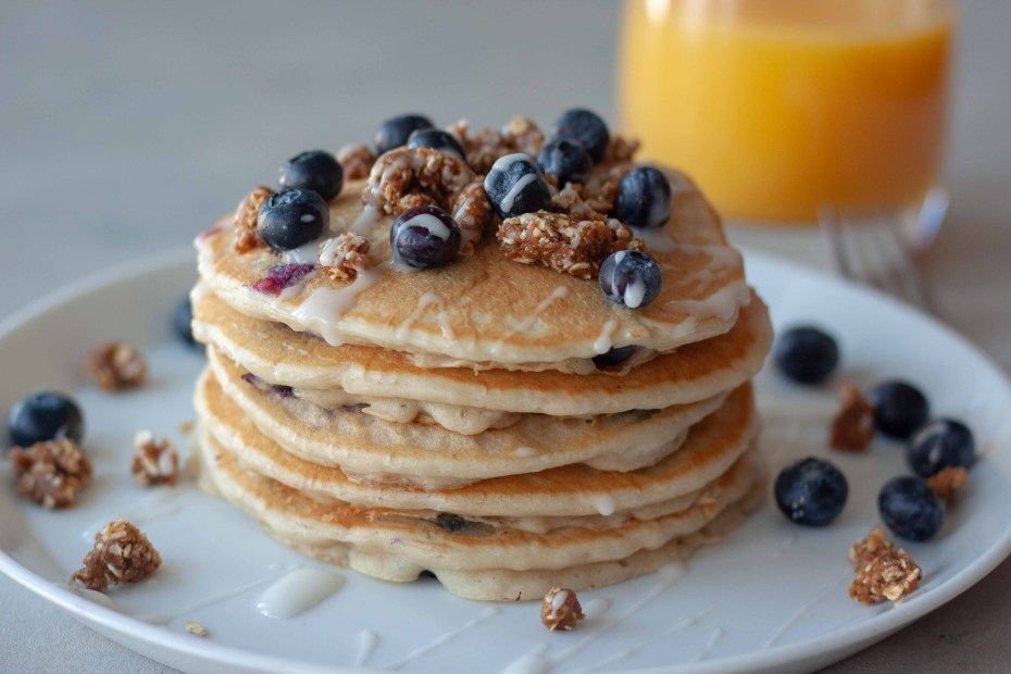 Plate of Blueberry Streusel Pancakes and glass of orange juice.