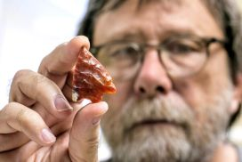 Volunteer Bob Austin holds a red chert (silicified coral) projectile point from Hillsborough County that was used at the end of a spear or knife.