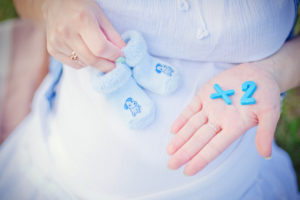 """pregnant belly with woman holding baby shoes and """"x2"""" blocks"""