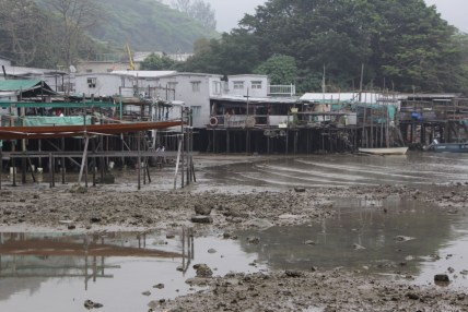 Ho Jeon Pak collects small fish and shrimp in front of his stilt house (left) in Tai O.