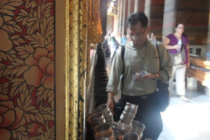 Sarunsiri wishes for luck by donating money in the Wat Pho Temple.