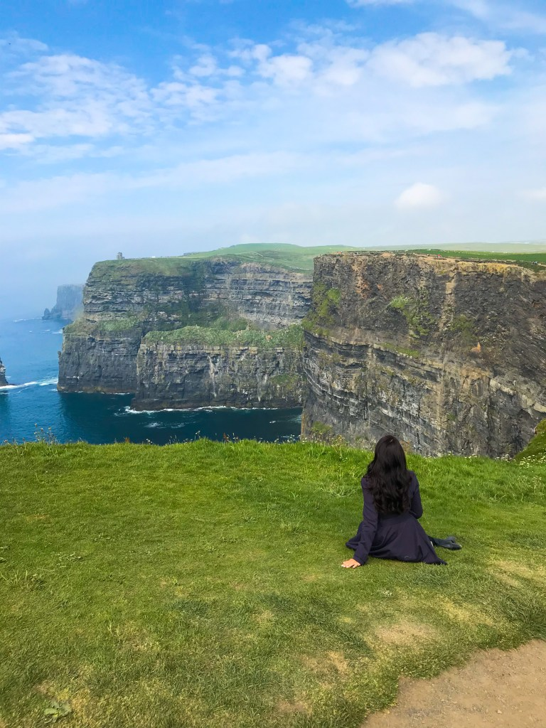 Woman staring at Cliffs of Moher in Ireland