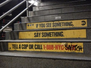 An example of a grassroots beautification project, with graffiti covering part of a police message that encourages snitching in New York City.