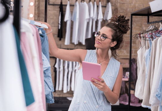 Female retail employee adjusting clothing on store shelves while holding mobile device.