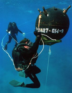 970215-N-3093M-001 Aviation Ordnanceman 1st Class David Ahearn (Diver) attaches an inert ÒSatchel ChargeÓ to a training mine, during exercises in waters off Naval Base Guantanamo Bay, Cuba. U.S. Navy Photograph by PhotographerÕs Mate 2nd Class Andrew Mckaskle (Released)