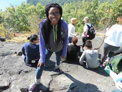 Codman Academy student smiles on top of ledge during Merrowvista school program