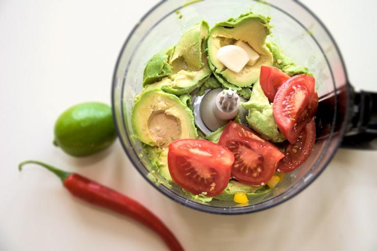 Guacamole avocado tomaat peper limoen in keukenmachine