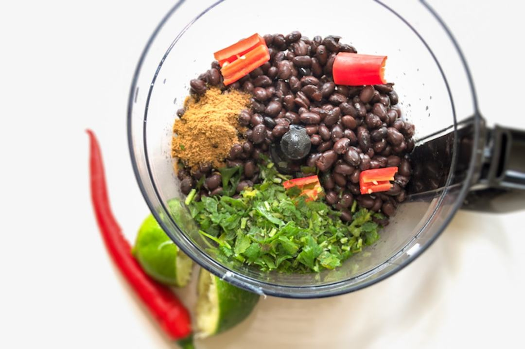 Zwarte bonen dip koriander limoen rode peper in keukenmachine