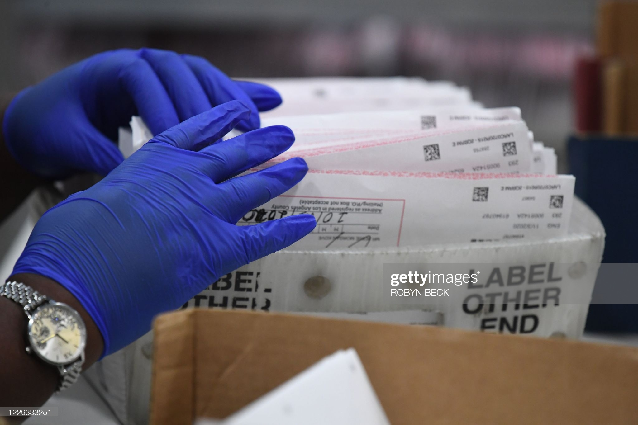Election workers extract mail-in ballots from their envelopes and examine the ballot for irregularities at the Los Angeles County Registrar Recorders' mail-in ballot processing center at the Pomona Fairplex in Pomona, California, October 28, 2020. - Officials relocated mail-in ballot processing to the expansive location due to the need for COVID-19 social distancing for the ballot workers and the large number of mail-in ballots. While the tabulation of votes cast for Donald Trump and Joe Biden will begin when polls close on November 3 at 8pm, envelopes are now being sorted and signatures and ballots verified to expedite the tabulation process on November 3. (Photo by Robyn Beck / AFP) (Photo by ROBYN BECK/AFP via Getty Images)
