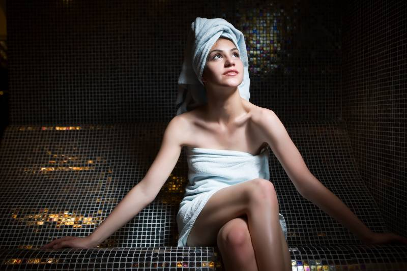 Spa woman.Beautiful girl after bath in jacuzzi spa,relaxing after massage,wrapped in towels.Skincare.Perfect smooth young exfoliated skin.Woman pleased with the results from the spa treatments