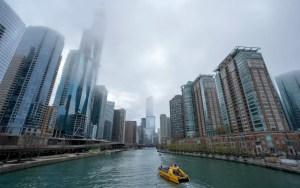 yellow boat sailing between large buildings