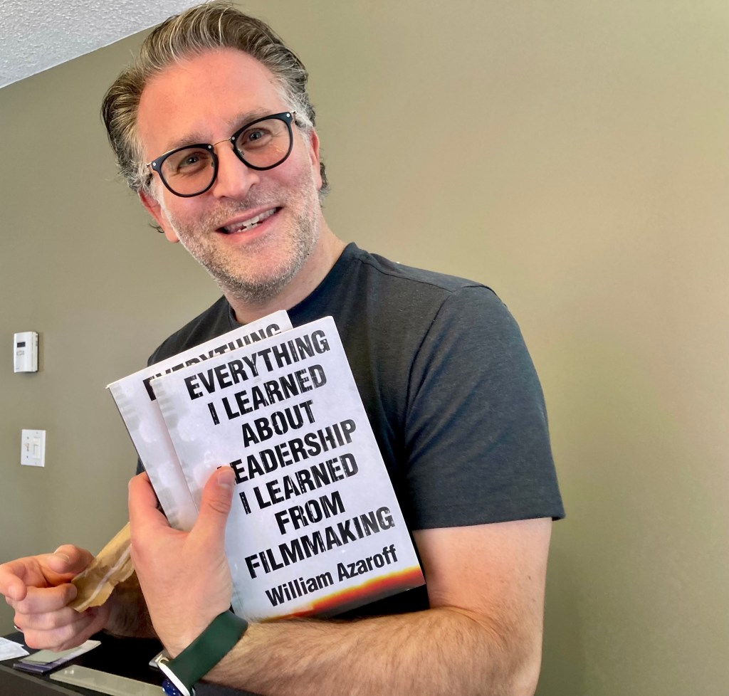 Holding a copy of my new book.