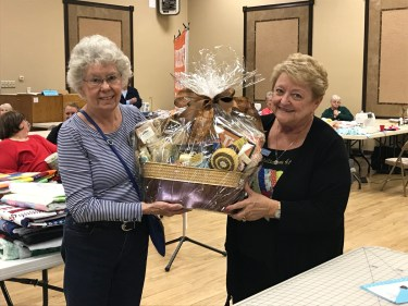 Hilda T (left) from our host community wins the door prize basket, made by our talented Letty (right)..