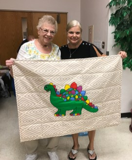 Carol (left) and Lynn (right) showing an extra special quilt from the 100+ blankets Carol made for us this year!