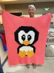 Brenda C, with her penguin blanket. Look at those adorable heart feet.
