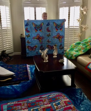 Carol displaying a beautiful butterfly quilt with quilt stacks all around.
