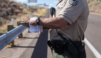 A Navajo County Sheriff reserve deputy fills out paperwork after pulling over a car and searching it for drugs on November 22, 2016 in Holbrook, Arizona. Navajo County uses forfeiture money to fund the salaries of its drug task force. (Photo by Emily L. Mahoney/Arizona Center for Investigative Reporting)