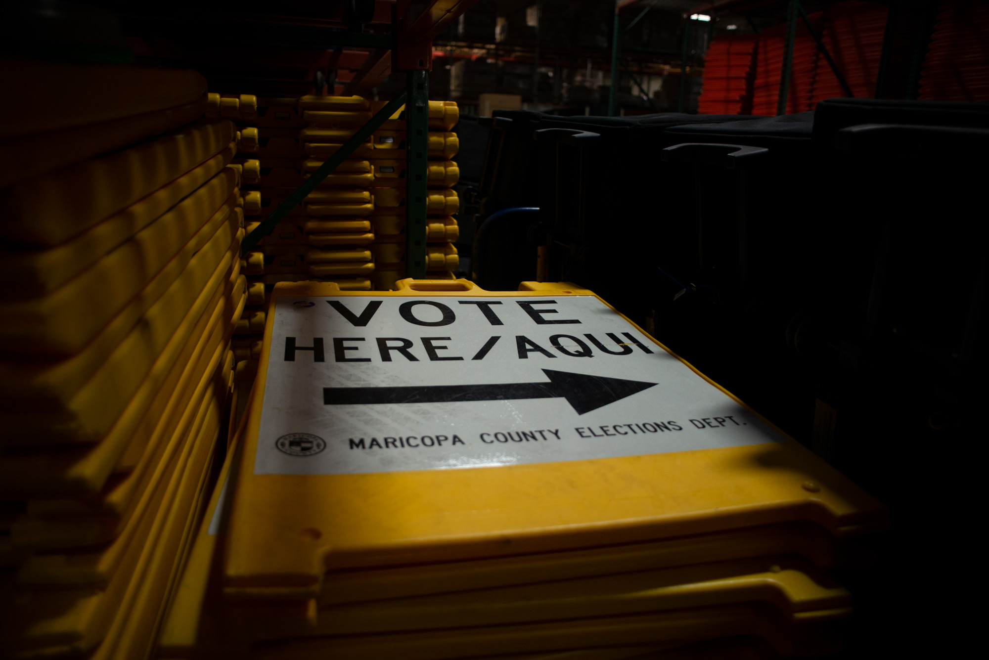 """Yellow """"Vote Here"""" signs are stacked on large metal shelving units within a warehouse at the Maricopa County Tabulation and Election Center in downtown Phoenix on Sept. 25, 2020."""
