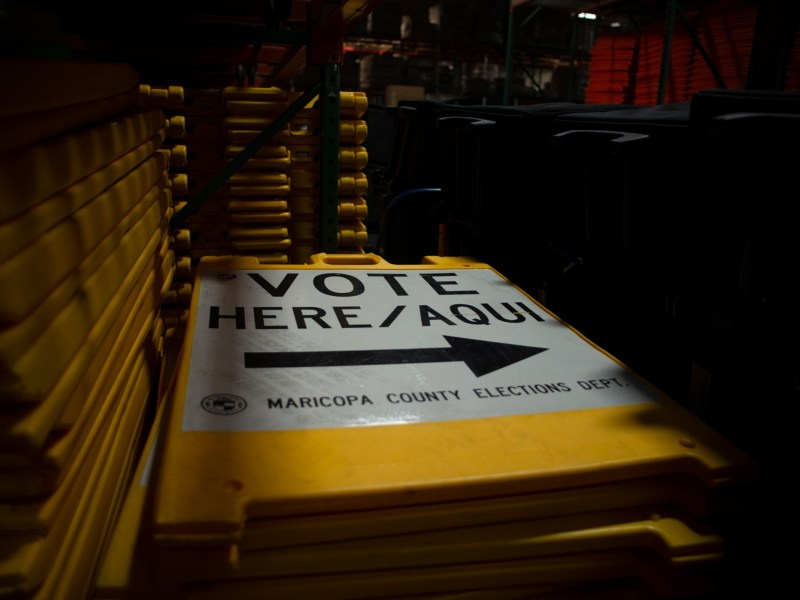 "Yellow ""Vote Here"" signs are stacked on large metal shelving units within a warehouse at the Maricopa County Tabulation and Election Center in downtown Phoenix on Sept. 25, 2020."