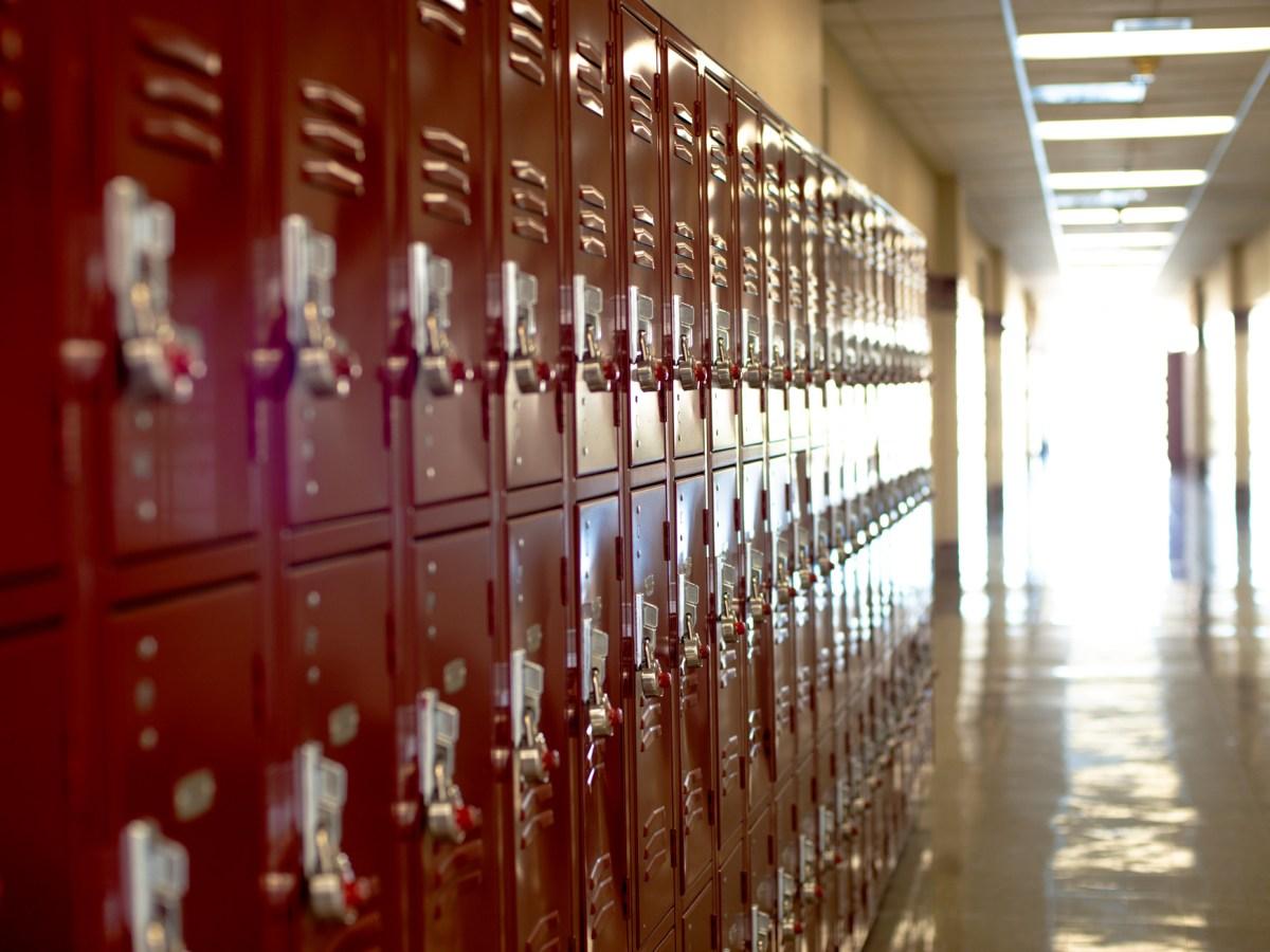 red lockers along a wall in an empty school hallway
