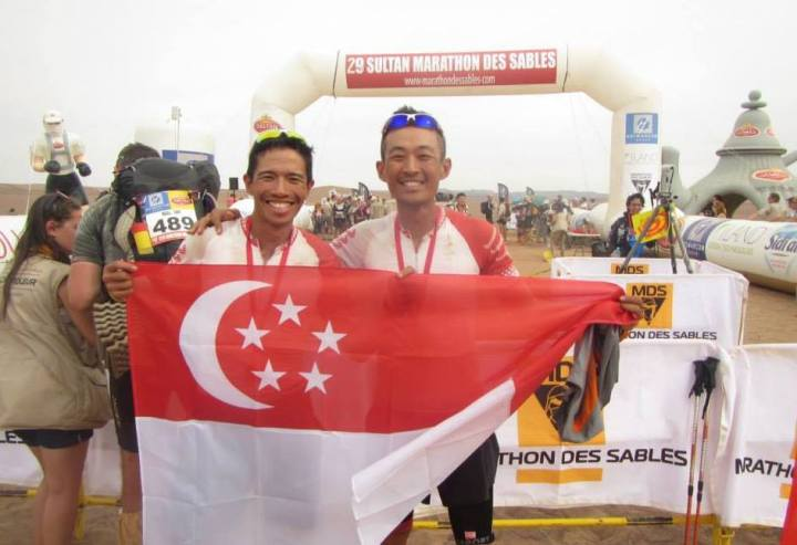 Ian and Wei Chong flying the flag proud and high at the Marathon Des Sables finishing line.