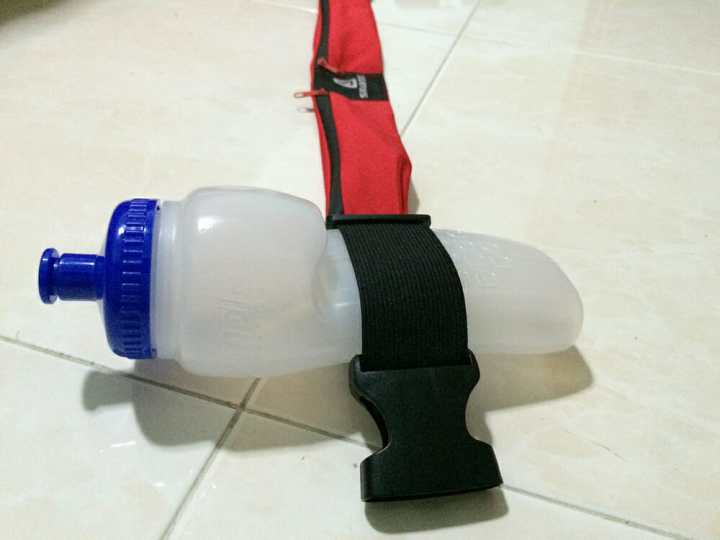 The Simple Hydration bottle slotted between the belt adjuster.