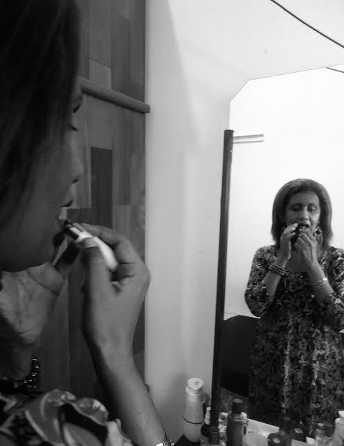 #PraCegoVer: Na foto em preto e branco, ao lado esquerdo, vemos os contornos do rosto de Rosiane. Ela passa batom nos lábios. À direita, o reflexo dela no espelho: negra, cabelos castanhos, trajando um vestido com mangas. Foto: Lorena de Paula