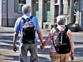Two elderly people walking down the street