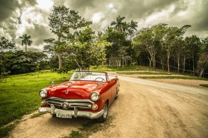 Red convertible car on dirt road.